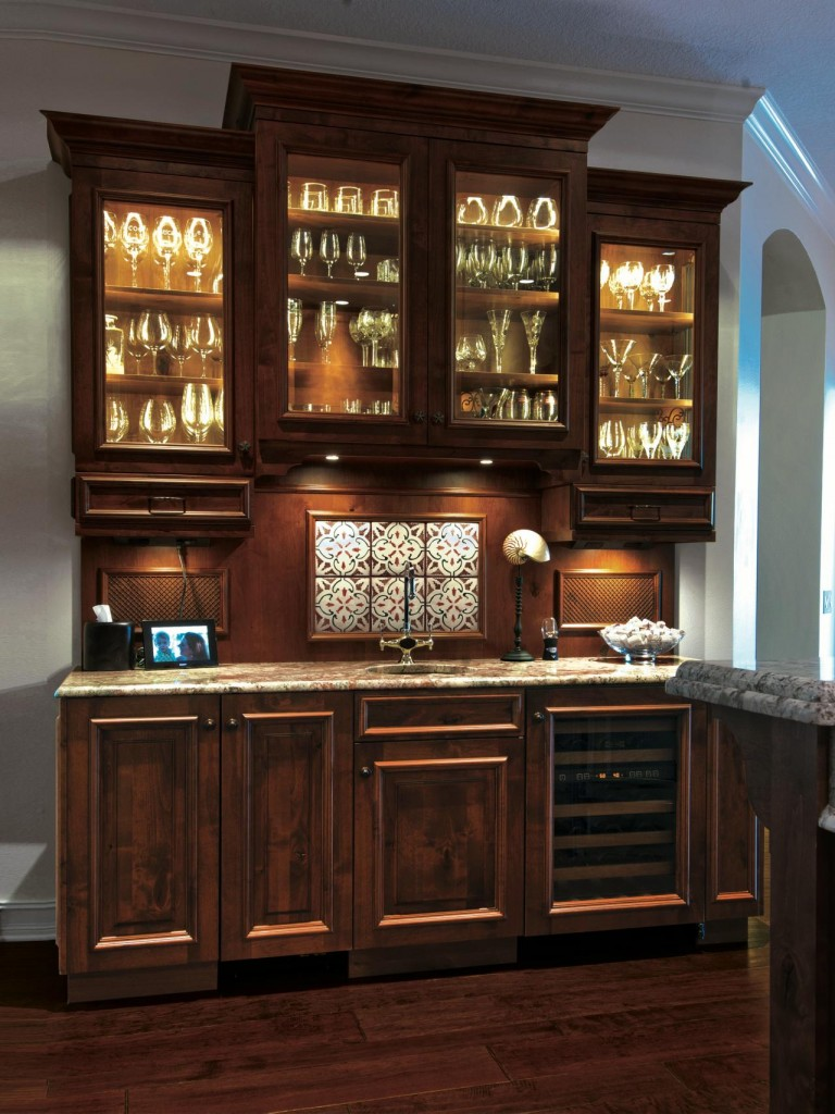 Traditional dry bar with glass-front cabinets, inner-cabinet lighting, and under-cabinet lighting. | Photo Source: HGTV