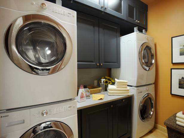 Compact laundry room with stacked double washer and dryer, and dark shaker cabinetry, such as our Pepper Shaker line. | Photo Source: HGTV