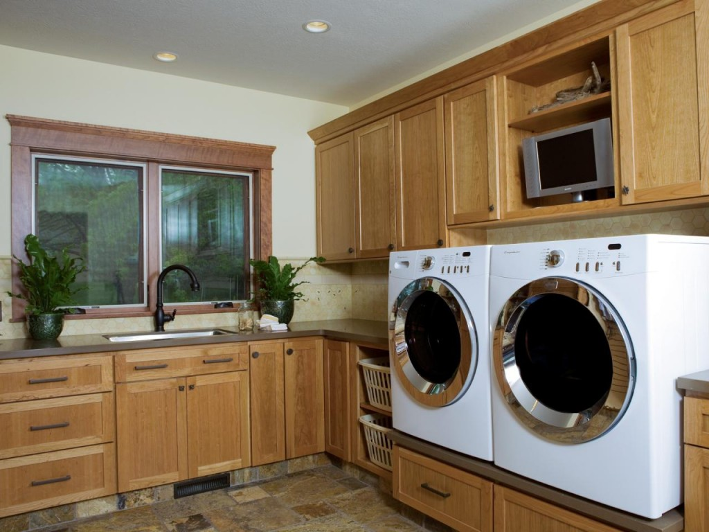 Simple laundry room with  elevated side-by-side washer and dryer, a sink, cabinets, and drawers. Get a similar look with classic Country Oak cabinets. | Photo Source: HGTV