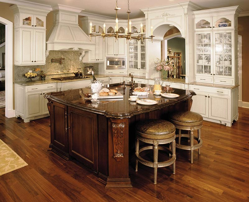 This updated take on Old World features two-toned cabinetry, corbels, warm metal fixtures and other intricate accessories and decor. | Photo Source: blogkitchens.com